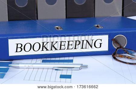 Bookkeeping - blue binder on desk in the office