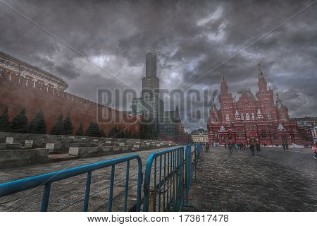 The Kremlin wall and the Red Square in uncertainty fog under gloomy clouds
