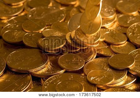 Gold Eagle one ounce coins being poured down onto a pile of other golden money suggesting immense wealth