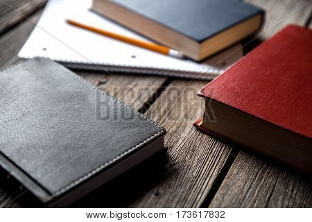 Business concept ideas book and exercise book on a wooden background with pencils