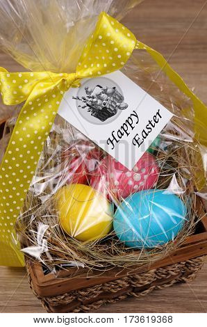 Colorful eggs stacked hay in cellophane gift basket for Easter