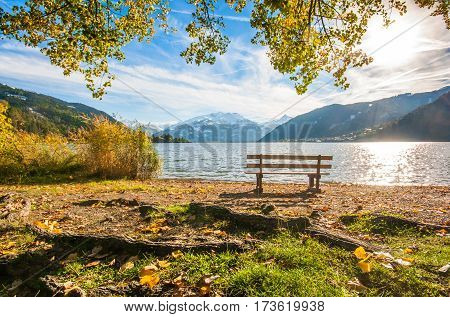 Beautiful autumn scene with park bench and mountain lake in the Alps Zell am See Salzburger Land Austria