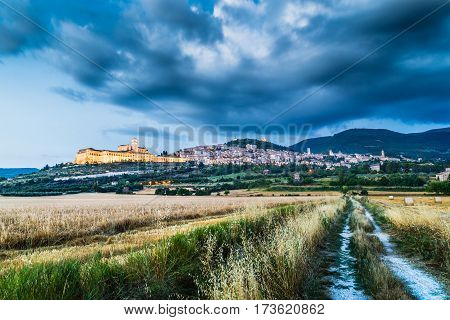 Beautiful View Of The Ancient Town Of Assisi With Dramatic Cloudscape During Blue Hour, Umbria, Ital