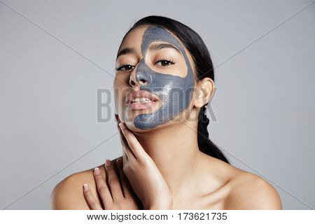 mixed race woman with gray clay facial mask. facial treatment. Coal black mask
