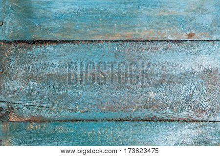 Vintage wood background with peeling blue paint.