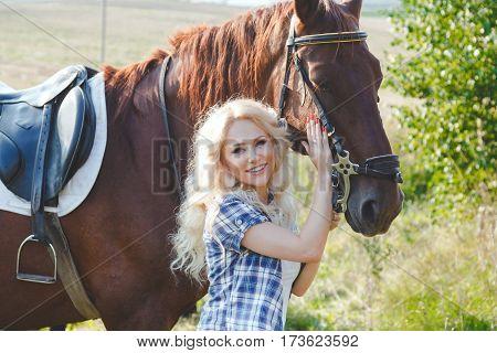 Beautiful blonde girl in blue plaid shirt hugging her brown horse.