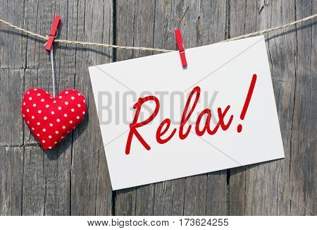 Relax - postcard with red heart on wooden background