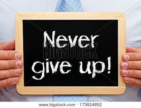 Never give up - Businessman holding chalkboard with text