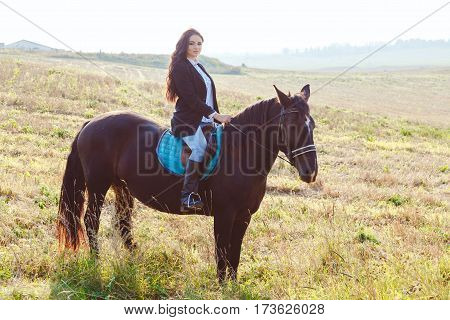Gorgeous brunette girl wearing fashionable riding a horse in the field