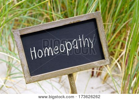 Homeopathy - chalkboard with beach and green grass as background