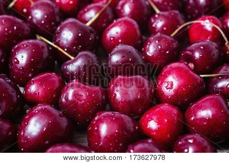 Background of ripe red cherry with water drops. Healthy eating. The texture of berries. Cherry background