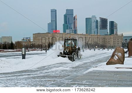 Moscow Russia - December 12 2016: Snowplow cleans from the road snow in Victory park in Moscow