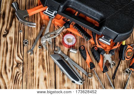 A toolbox with different instruments. A set of tools on a wooden background.