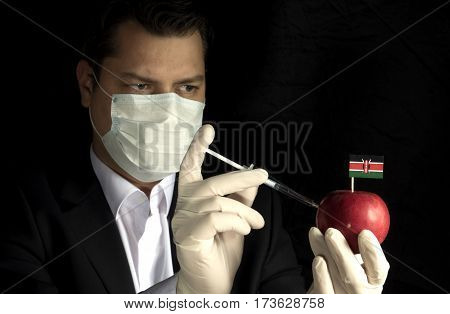 Young Businessman Injecting Chemicals Into An Apple With Kenyan Flag On Black Background