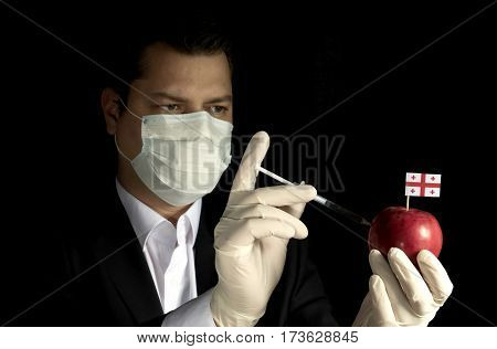 Young Businessman Injecting Chemicals Into An Apple With Georgian Flag On Black Background