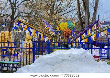 Children's playgrounds and children's rides in the winter on a holiday Maslenitsa