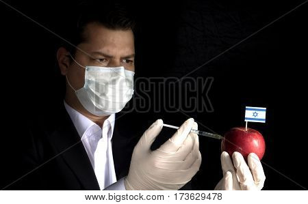 Young Businessman Injecting Chemicals Into An Apple With Israeli Flag On Black Background