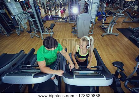 Personal trainer man with athletic girl on a treadmill in the gym. Top view.