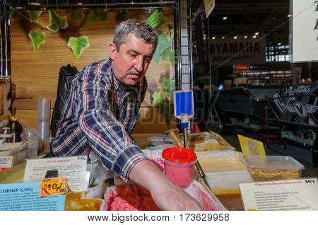 Moscow, Russia - February 25, 2017: Gray-haired man seller of home produced honey at the fair puts the goods on the table and waiting for buyers