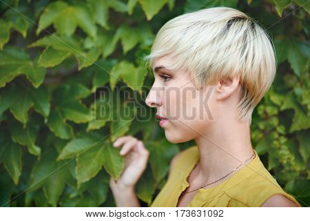 Portrait of an urban boyish blonde millennial girl looking away and being serene in front of a leafy background.