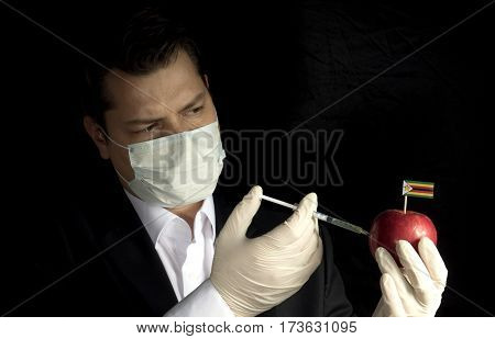 Young Businessman Injecting Chemicals Into An Apple With Zimbabwean Flag On Black Background