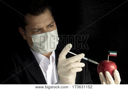 Young Businessman Injecting Chemicals Into An Apple With Kuwaiti Flag On Black Background
