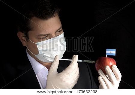 Young Businessman Injecting Chemicals Into An Apple With Argentine Flag On Black Background