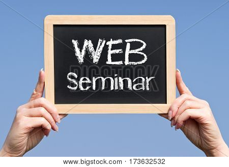 WEB Seminar - female hands holding chalkboard with text
