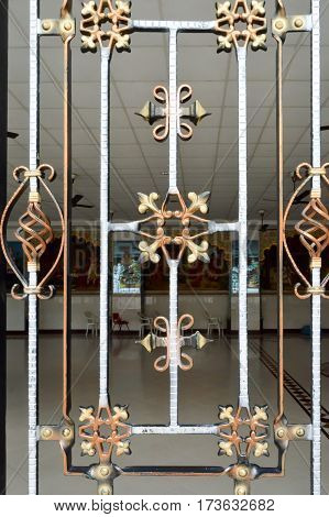Wrought iron grid with gildings separate the entrance hall and the prayer room from a Hindu temple