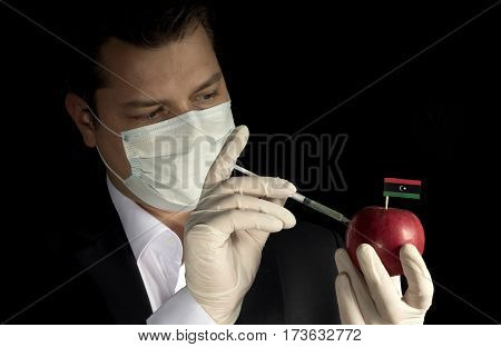 Young Businessman Injecting Chemicals Into An Apple With Libyan Flag On Black Background