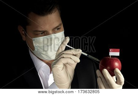 Young Businessman Injecting Chemicals Into An Apple With Singaporean Flag On Black Background