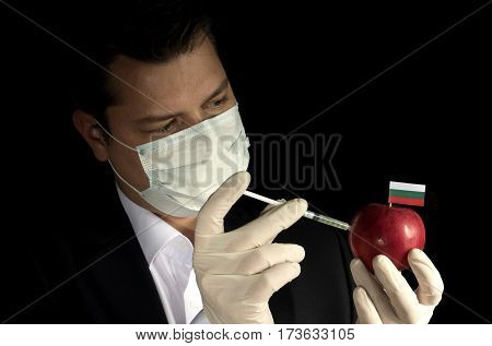 Young Businessman Injecting Chemicals Into An Apple With Bulgarian Flag On Black Background