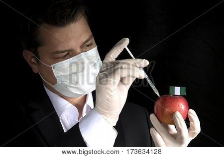 Young Businessman Injecting Chemicals Into An Apple With Nigerian Flag On Black Background