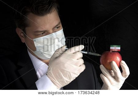 Young Businessman Injecting Chemicals Into An Apple With Iranian Flag On Black Background
