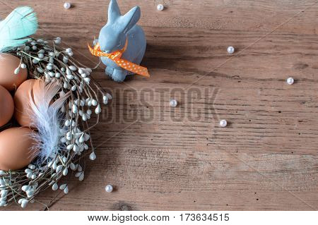The traditional symbol of the Easter. Brown eggs in the nest and funny Easter`s rabbit. Traditional holiday decorate.