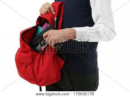 Schoolboy hiding gun in backpack on white background