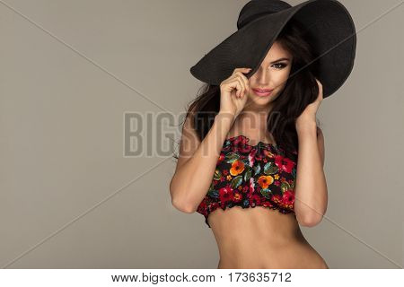 Sexy fit young woman wearing summer black hat with large brim