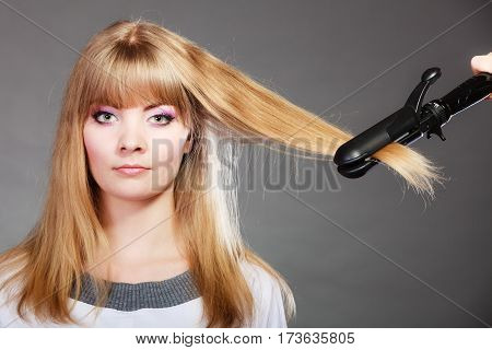 Hairstyling. Attractive blonde woman long haired making hairstyle hairdo with electric hair iron straightener gray background