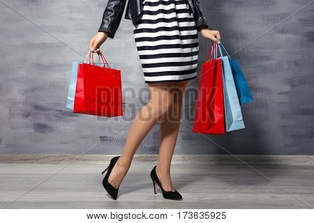Woman with shopping bags on grey wall background