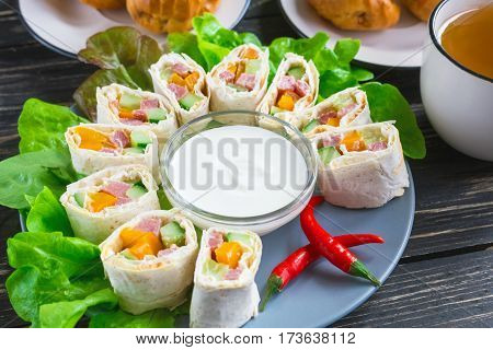 Pita Rolls With Lettuce, Sauce, Chili Pepper, Eclairs And Tea