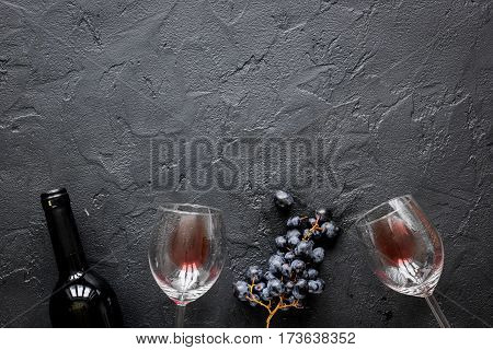 Glass bottle of red wine with fresh grapes on stone table background top view mock up