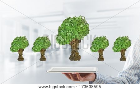 Close of businessman holding tablet pc with green tree made of gears and cogwheels. Mixed media