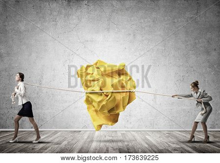 Two businesswomen playing tag of war game