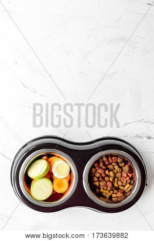 Fresh vegetables and dry petfood on white kitchen table background top view mock up