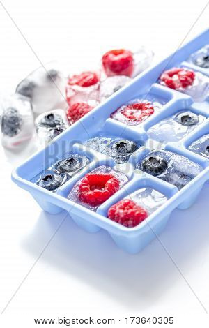 Blue ice tray with ice cubes and ripe berries on white background