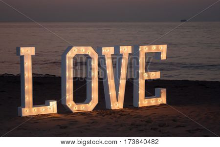 The four letters of the word love illuminated and staked into the sand on a beach