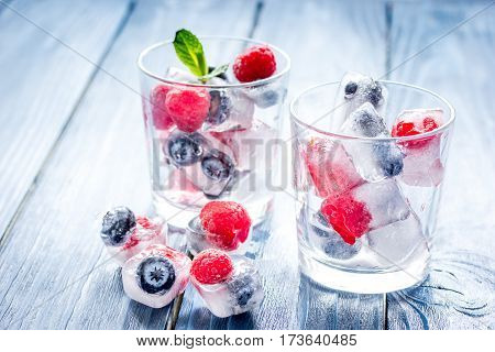 Ice cubes with frozen blueberry and raspberry and mint in glass on blue wooden table background