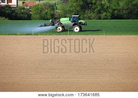 Tractor Fertilizes Green Wheat Field