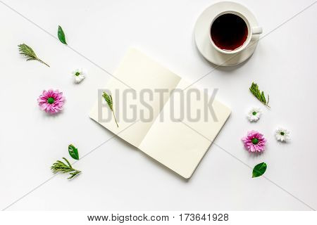 Open notebook with cup of black coffee and flowers on white background top view mockup
