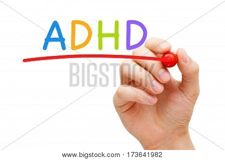 Hand writing ADHD Attention Deficit Hyperactivity Disorder with marker on transparent glass board.